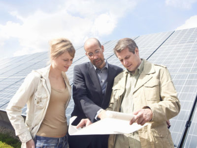 Engineer with plans meeting couple standing next to solar panels